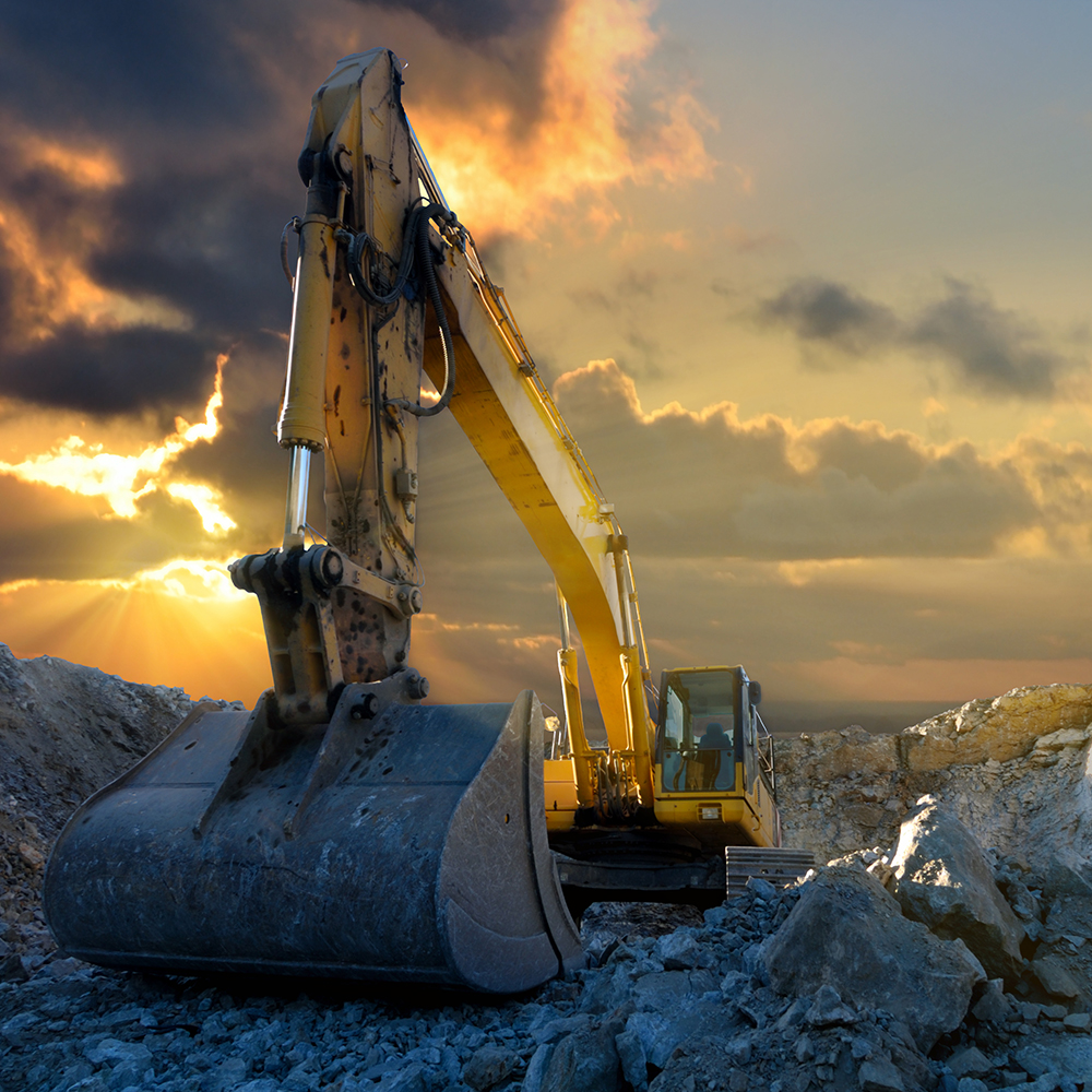 Image of a tracked excavator in a quarry with a setting sun and light rays
